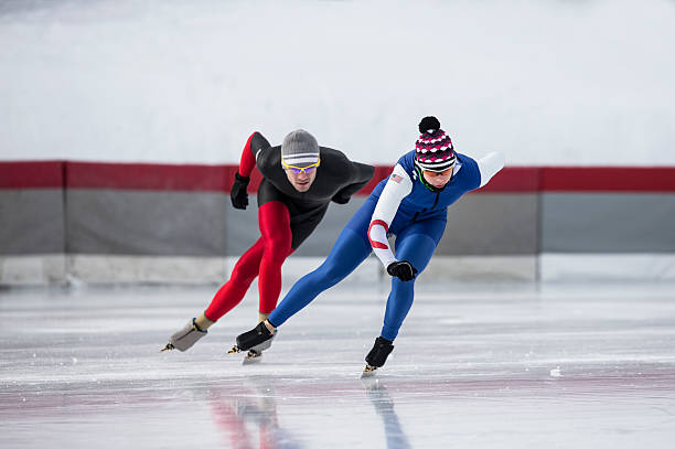 A woman and man speed skating on a cold winter day.